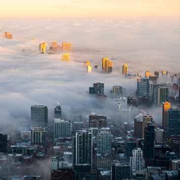 photo of cityscape covered in fog - Photo by AJ Nakasone