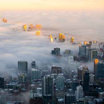 photo of cityscape covered in fog - Photo by AJ Nakasone